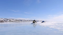 Snowmobiles towing qamutik through melt pond at Admiralty Inlet. Stock Footage