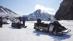 Small Arctic expedition team taking a rest next to a large mountain range. Stock Footage