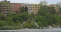 People Distantly are Walking at the River Red Yellow Houses Buildings on The Stock Footage
