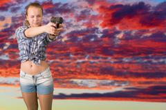 Teen girl aiming from the gun Stock Photos