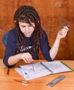 The girl student working with school exercises on the table - stock photo