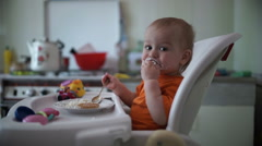 Stock Video Footage of Little boy practices eating in the kitchen 7  - Without color correction