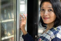 Woman chooses snack from vending machine Stock Photos