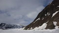 An Arctic mountain range surrounding an ice field. (Pan) Stock Footage