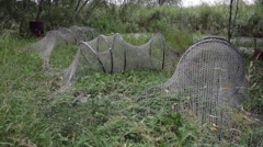 Fishnet drying on yard, bag-shaped fishing net, hoops, capture, trap Stock Footage