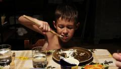 Village boy eating pancakes with wooden fork in an old house, old time Stock Footage