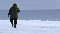 Man standing on the Arctic shoreline with a harpoon. Stock Footage