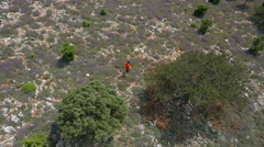 Aerial - High angle view of a young man running down the hill Stock Footage