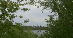 Tube of Factory Distantly on The Opoosite Bank of River Factory among the Trees Stock Footage