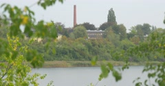 Red Tube of Factory on The Opoosite Bank of River Factory among the Trees Green Stock Footage