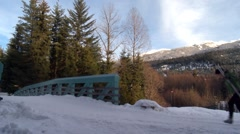 Skiers cross over a bridge in Whistler, British Columbia. - stock footage