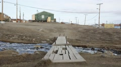 Bridge stretching over a stream running through Pond Inlet. Stock Footage