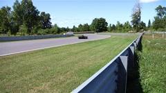 A black race car heads into a corner at Calabogie Raceway. - stock footage