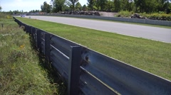 A blue race car speeds towards the camera on a straightaway at Calabogie Stock Footage