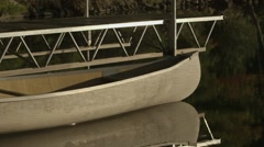 A canoe floating beside the dock it is tied upon. Stock Footage