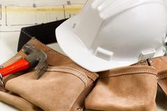 Construction contractor tools with blue print drawings in background Stock Photos