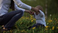 Mother raises a little boy sitting on the grass Stock Footage