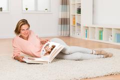 Young Woman Smiling While Looking At Photo Album In Living Room Stock Photos
