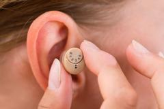 Close-up Of Female Hands Putting Hearing Aid In Ear Stock Photos