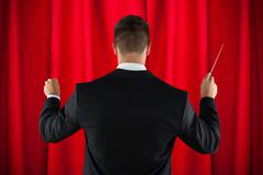 Stock Photo of Rear View Of Male Orchestra Conductor Directing With His Baton
