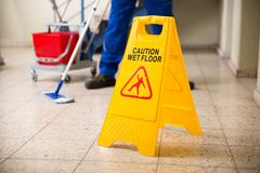 Low Section Of Worker Mopping Floor With Wet Floor Caution Sign On Floor Stock Photos