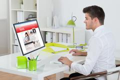 Young Businessman Watching Online News On Computer At Workplace Stock Photos