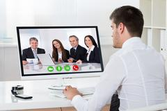 Businessman Videoconferencing With Co-workers On Desktop Computer At Desk Kuvituskuvat