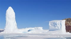 Iceberg on sea-ice with mountains in the background near Admiralty Inlet. - stock footage