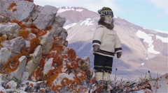 Handmade inuit doll displayed on rocks near a mountain in Arctic Bay, Nunavut. Stock Footage