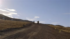 Two kids walking biking up a hill in Arctic Bay, Nunavut. Stock Footage