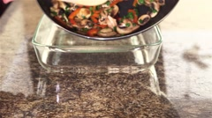 Spreading sauteed vegetables along the bottom of a pan. - stock footage