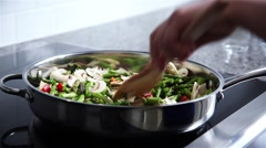 Vegetables being sauteed and mixed in a frying pan. - stock footage