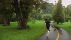 A man running on the bike paths in Ottawa going through the Arboretum on a rainy Stock Footage