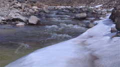 Runoff stream flowing quickly from a mountain in Arctic Bay, Nunavut. (Tilt Up) - stock footage