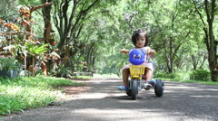 The two-year old cute asian girl riding a toy car alone on street Stock Footage