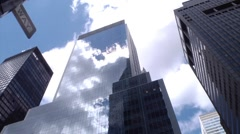 A large glass skyscraper reflects the sun and clouds in New York City. Stock Footage