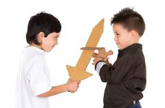 Stock Photo of Two small boys simluating sword fight using toys and homemade shield, white