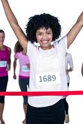 Portrait of happy winner female athlete crossing finish line with arms raised Stock Photos