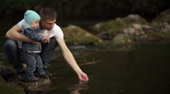Father with little son playing on the river bank with water 3 Stock Footage