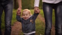 Young family walking in the park, father, mother and son - stock footage