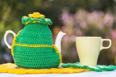Knitted doily on the teapot on  natural background. - stock photo