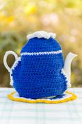 Knitted doily on the teapot in  natural background. - stock photo