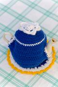 Knitted doily on the teapot in  natural background. Stock Photos