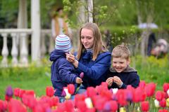 Mother And Children Relaxing around  flower beds - stock photo