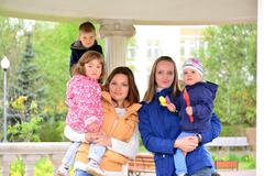 Two mothers with children on the walk in  gazebo - stock photo