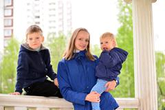 Mother with two children on  walk - stock photo