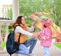Mother  with her daughter and  umbrella in arbor - stock photo