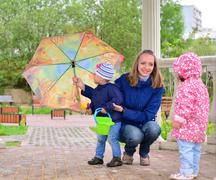 Mother with children and an umbrella in arbor - stock photo