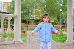 Cute baby girl with blonde curly hair outdoors.  2-3 year old. Stock Photos