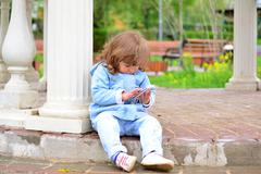 Girl two years, with a cell phone in the park Stock Photos